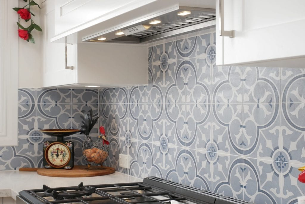 Dramatic two tone kitchen Blakehurst where the integrated Siena rangehood is perfectly decorated by the hand crafted black and blue tiled splashback
