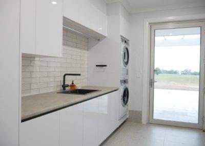 Modern white kitchen Razorback laundry with subway tile splashback