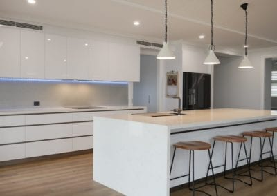 Modern white perfection kitchen Razorback with white stone waterfall benchtops and three handing pendant lights
