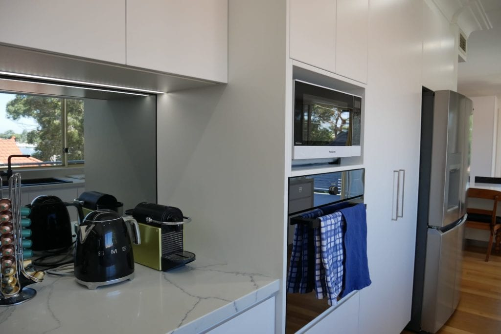 Streamlined glamour kitchen Blakehurst where the black mirror splashback allows the stunning view to enter the kitchen