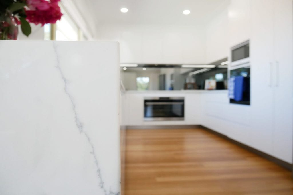 Streamlined glamour kitchen Blakehurst uses 40mm mitred stone waterfall edges to add a touch of glamour
