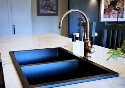 Dramatic two toned kitchen in Bowral black matte sink and brass tapwear
